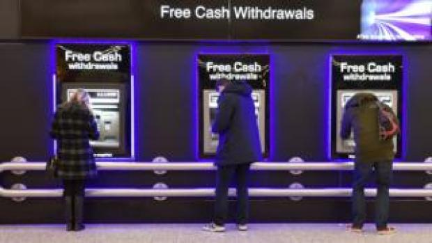 Three people standing at cashpoints