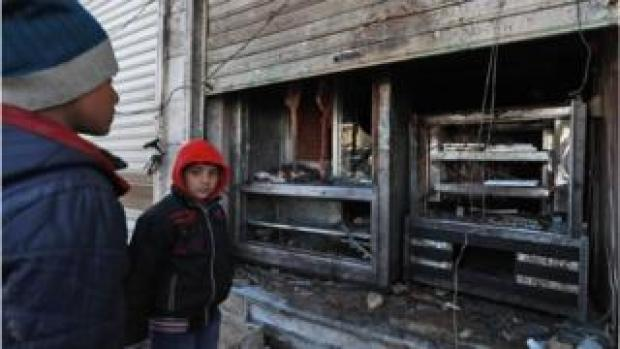 Syrian boys look at the destroyed grills outside a shuttered-down restaurant which was the site of a suicide attack targeting US-led coalition forces in the flashpoint northern Syrian city of Manbij