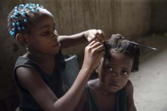 A Mozambican girl sits patiently as another girl braids her hair at a temporary shelter, following the Cyclone Idai in Beira, Mozambique, on 1 April 2019