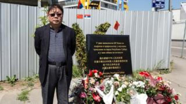 Shen Hong stands in front of the memorial