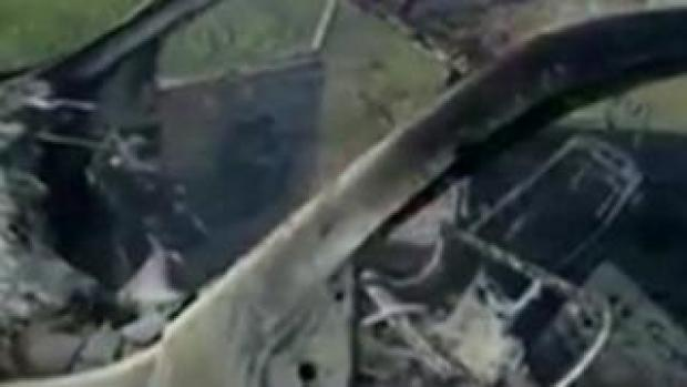 Still from video of burnt-out car