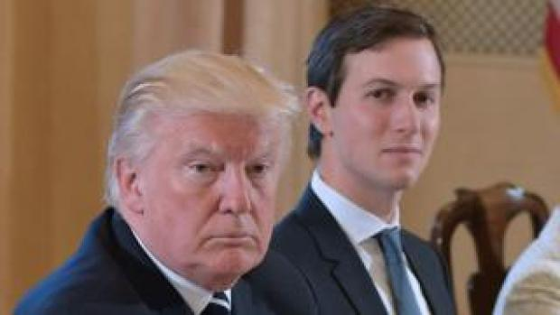 Jared Kushner, right, is seen over the shoulder of President Donald Trump - both seated at a table during an official meeting