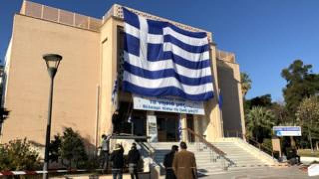 """Banner at the municipal theatre on the Greek island of Lesbos reads: """"We want our islands back, we want our lives back."""""""