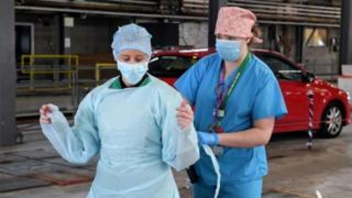 Medical staff put on their personal protective equipment (PPE) at an MOT testing centre in Belfast, Northern Ireland