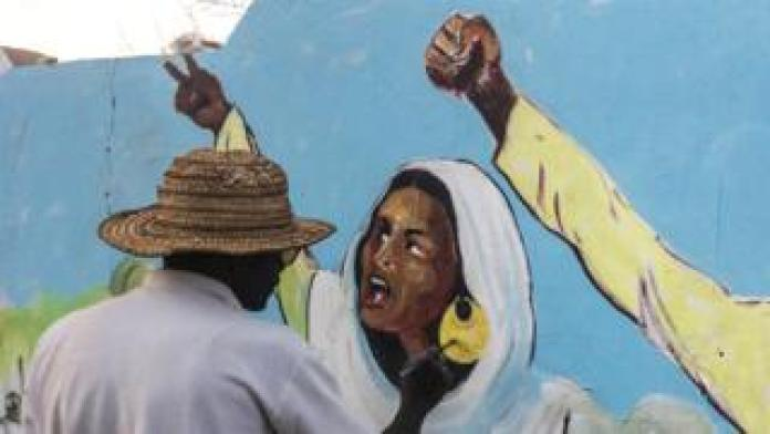 An artist painting a mural of Alaa Salah, the 22-year-old student protester, in Khartoum, Sudan
