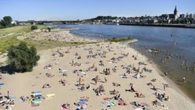 People enjoy the warm weather in the Waal river in Nijmegen, The Netherlands