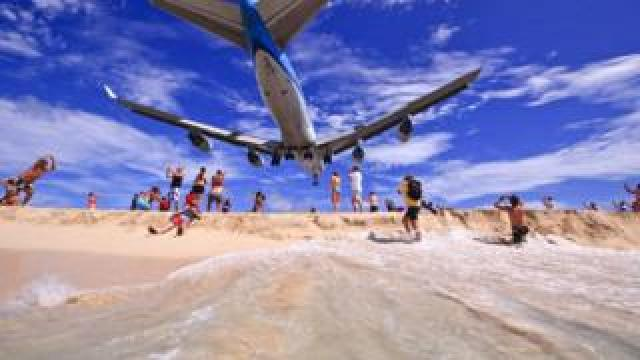 A low-flying plane with blue livery passes overhead on a beach at Princess Juliana airport, Sint Maarten