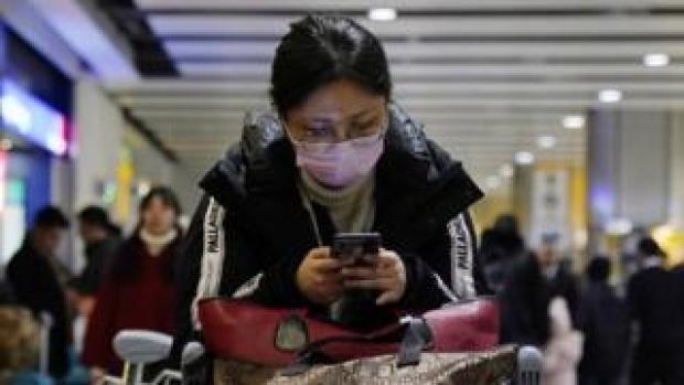 A passenger arrives wearing a mask at Terminal 4, Heathrow Airport, London