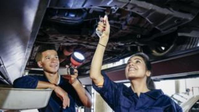 Two mechanic students repairing a car
