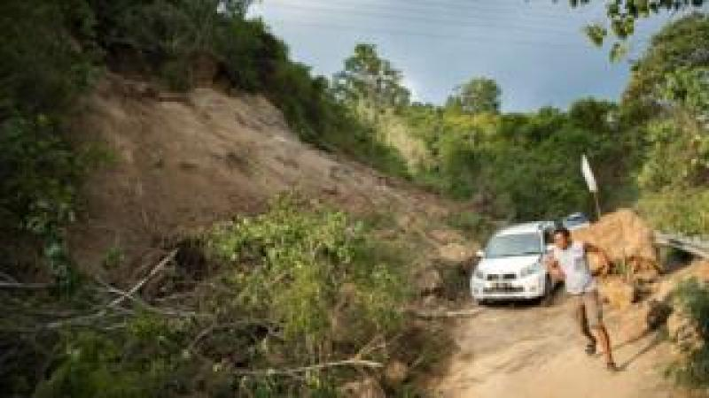 Vehicles drive along a road affected by a landslide on the outskirts of Palu in Central Sulawesi on September 29, 2018