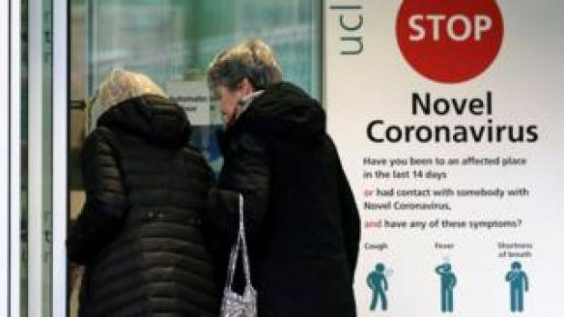 Two women walk past a sign providing guidance information about novel coronavirus (COVID-19) at one of the entrances to University College Hospital in London on March 5, 2020