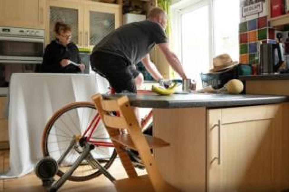 Man cycles on bike inside while wife does chores