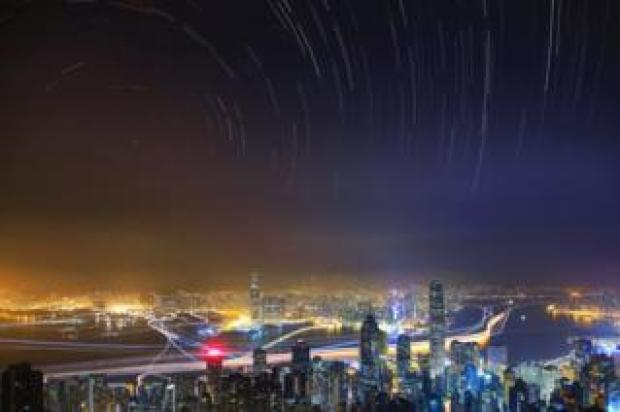 Taken from The Peak, the highest mountain on Hong Kong Island, the image shows the hustle and bustle of the city in contrast to the peaceful starry sky.