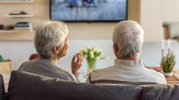 Two pensioners watching TV