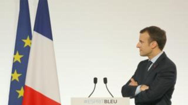 Emmanuel Macron staring at French and EU flags