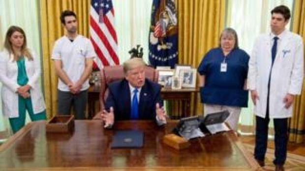 President Donald Trump in the Oval Office at the White House with nurses, 6 May 2020