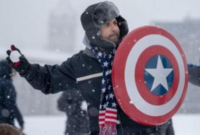 People participate in a snowball fight on the National Mall