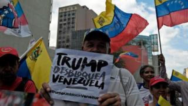 """A pro-government protester rallies against US sanctions with a sign reading """"Trump unblock Venezuela"""" in Caracas on August 7, 2019"""