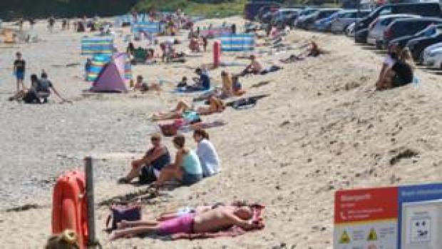 People relaxing and enjoying the sun at Maenporth Beach on May 30 in Cornwall
