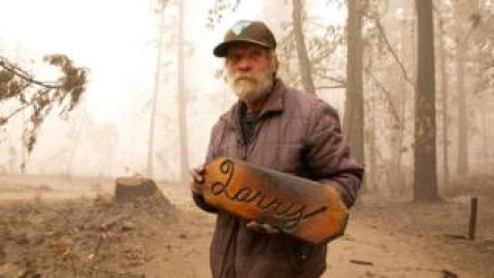 Man with plaque left from his destroyed cabin
