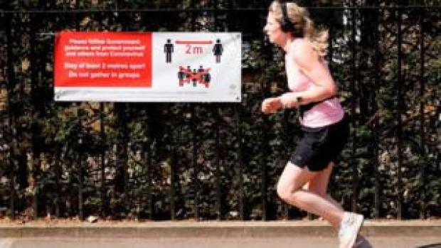 A runner running past a poster about social distancing