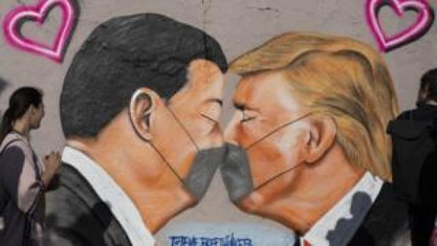 Street art shows US President Donald Trump and Chinese President Xi Jinping wearing protective mask and kissing at a section of the former Berlin Wall.