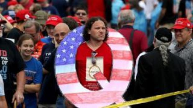 Man poses with a Q sign at a Trump rally