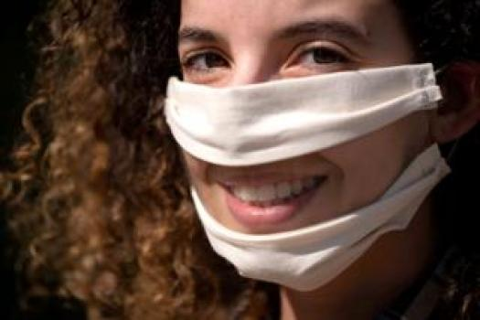 A woman wears a face mask that has a clear plastic panel over the mouth, so the mouth is visible for lip reading