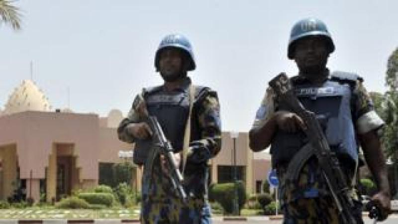 UN peacekeeper police officers stand guard at entrance of Hotel Salem in Bamako on March 8, 2015. T