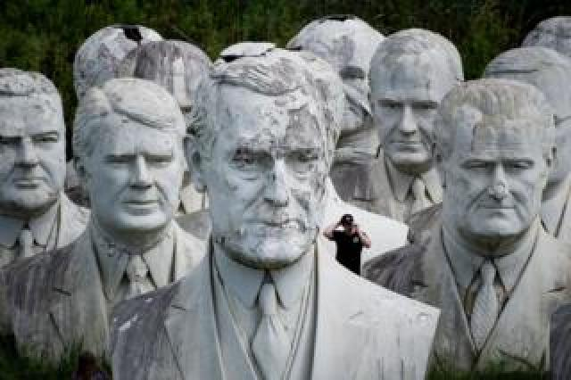A man stands behind a giant bust of US President Woodrow Wilson