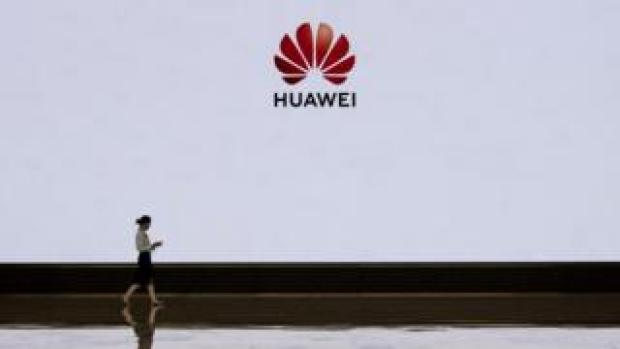 A member of Huawei's reception staff walks in front of a large screen displaying the logo