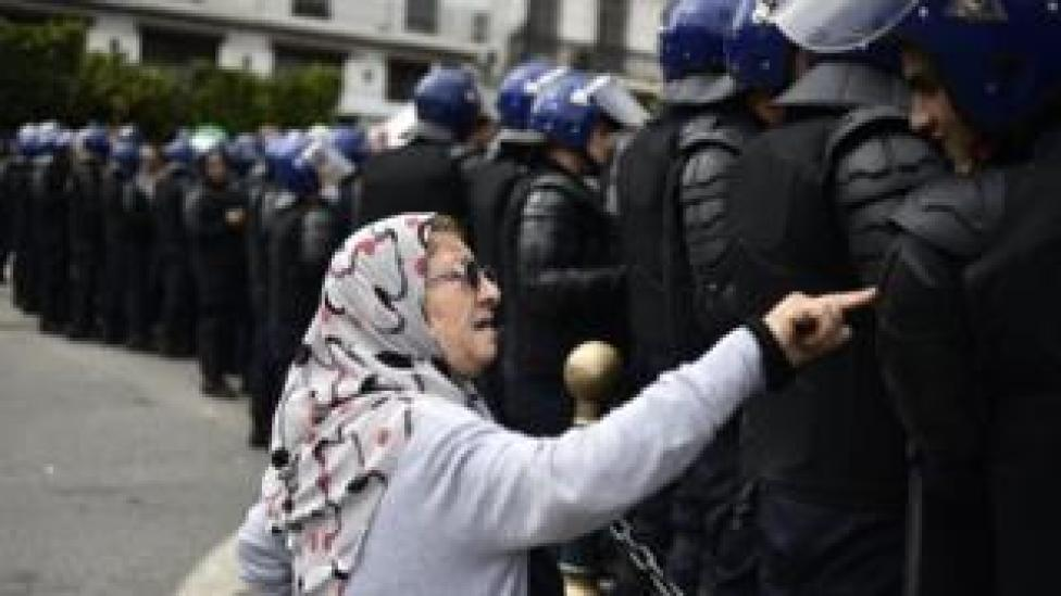An elderly Algerian woman talks to a member of the security forces cordoning-off a protest area during an anti-system demonstration in the capital Algiers on April 10, 2019. - Algerian demonstrators kept up protests today against the ruling elite despite a pledge from the interim head of state to hold 'transparent' presidential elections following veteran leader Abdelaziz Bouteflika's resignation. Lawmakers the day before selected upper house speaker Abdelkader Bensalah as Algeria's first new president in 20 years in line with constitutional rules, but the appointment failed to meet the demands of demonstrators pushing for the whole of Bouteflika's entourage to stand down.