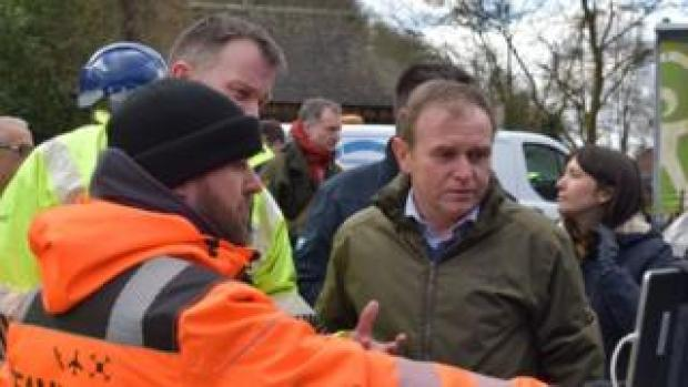 George Eustice views a screen showing drone camera images of flood defences during a visit to Ironbridge in Shropshire