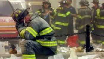 Firefighter pauses in rubble on World Trade Center (9/11/01)
