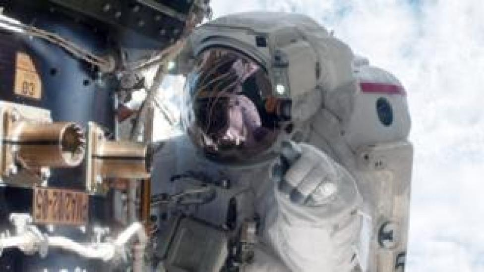 NASA astronaut Mike Fossum carries out maintenance during a space walk at the International Space Station