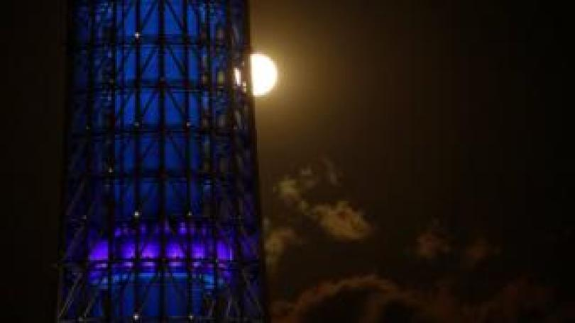 The full moon, also known as the Supermoon or Flower Moon, rises next to Tokyo Skytree in Japan