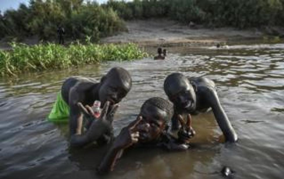 Sudanese boys pose for a picture as they bath in the shallow waters of the Nile River on May 1, 2019 at the Tuti island district of Khartoum