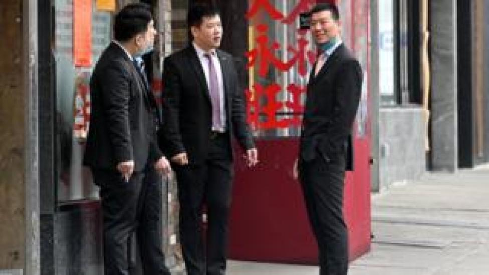 Men wearing suits are seen smoking on the sidewalk in Manhattan's Chinatown