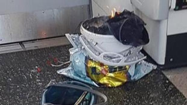 The device - a white bucket on fire inside a supermarket bag, with wires trailing on to the carriage floor
