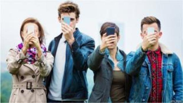 Four people holding their smartphones in front of their faces