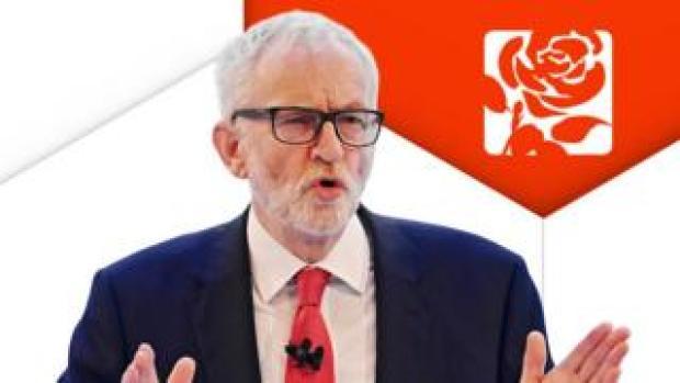 Jeremy Corbyn in front of Labour logo