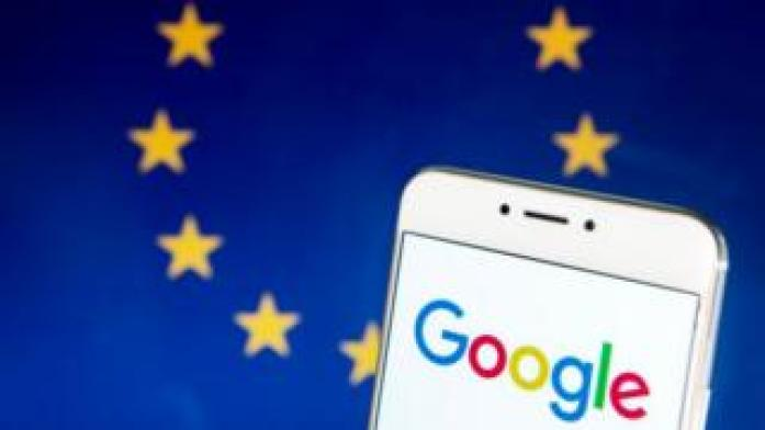 The Google logo on a smartphone with the EU flag in the background