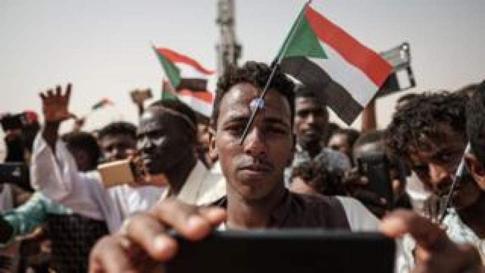 """A man poses for a """"selfie"""" photo with a cell phone while having a miniature Sudanese flag placed on his forehead with a plastic suction cap as he awaits the arrival of the deputy head of Sudan's ruling Transitional Military Council (TMC) and commander of the Rapid Support Forces (RSF) paramilitaries, during a rally in the village of Abraq, about 60 kilometers northwest of Khartoum, on June 22, 2019."""