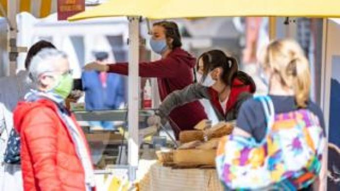 People wearing protective masks buy food at the city market in Lienz, Austria, on April 11, 2020