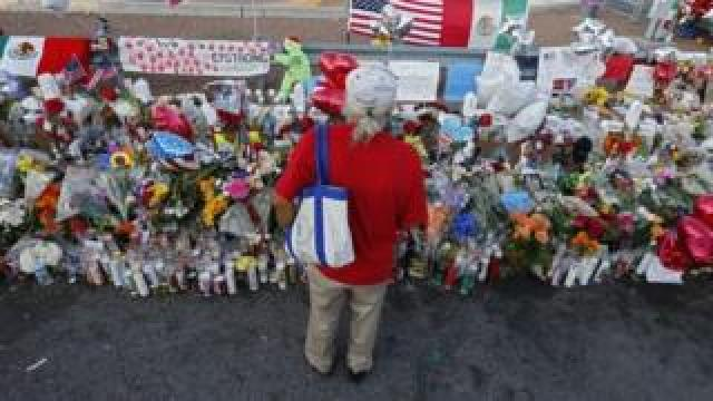 A woman stands over a memorial after a mass shooting in El Paso, Texas