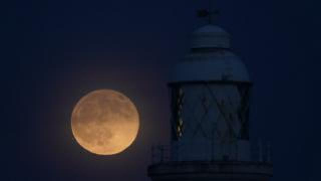 Wolf moon seen over St Mary's lighthouse at Whitley Bay in Northumberland