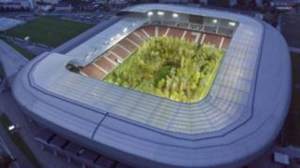 An aerial night shot of the stadium with the forest lit up by flood lighting