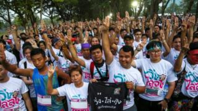 "Runners flash three finger salute as they attend at ""Run Against Dictatorship"" event at a public park in Bangkok"