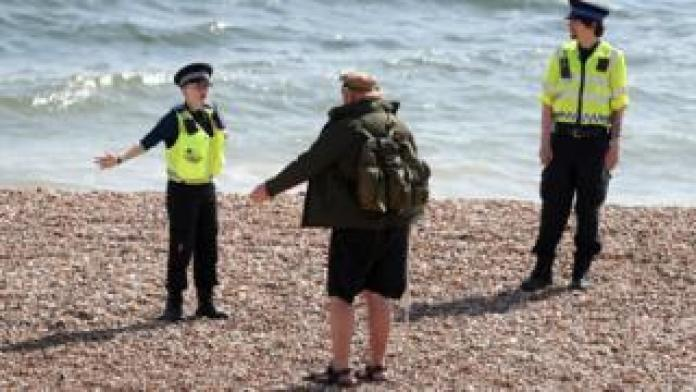 Police ask a walker on Briton Beach, East Sussex