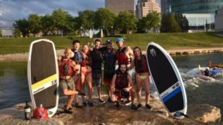 A groups of Dayton, Ohio surfers pose next to surfboards